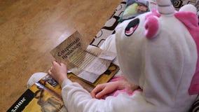 Μικρό κορίτσι που διαβάζει μια χαλάρωση βιβλίων σε έναν άσπρο καναπέ σ φιλμ μικρού μήκους