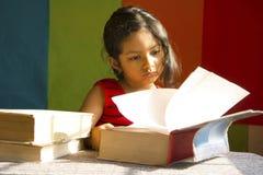Μικρό κορίτσι που διαβάζει τα μεγάλα βιβλία σαν είναι μελετητής, Pune, Maharashtra, Ινδία στοκ εικόνα