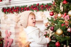 Μικρό κορίτσι που διακοσμεί το χριστουγεννιάτικο δέντρο κοντά στην εστία στοκ φωτογραφία με δικαίωμα ελεύθερης χρήσης