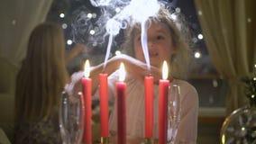 Μικρό κορίτσι που εκρήγνυται τα κόκκινα κεριά Χριστουγέννων απόθεμα βίντεο