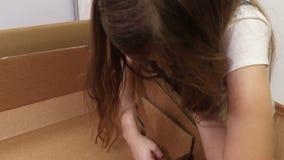Μικρό κορίτσι που ελέγχει το κουτί από χαρτόνι απόθεμα βίντεο