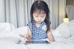 Μικρό κορίτσι που εναπόκειται στην ταμπλέτα στο ευτυχές χαμόγελο κρεβατιών χρησιμοποιώντας το Διαδίκτυο που προσέχει και που έχει στοκ εικόνες με δικαίωμα ελεύθερης χρήσης