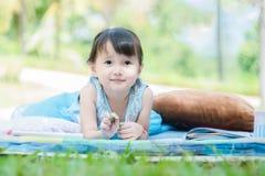 Μικρό κορίτσι που εναπόκειται στο βιβλίο σχεδίων στο χαλί στο πάρκο με το ευτυχές πρόσωπο όταν η μυοχαλαρωτική ουσία της στις δια στοκ φωτογραφία με δικαίωμα ελεύθερης χρήσης