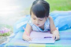 Μικρό κορίτσι που εναπόκειται στο βιβλίο σχεδίων στο χαλί στο πάρκο με το ευτυχές πρόσωπο όταν η μυοχαλαρωτική ουσία της στις δια στοκ φωτογραφία