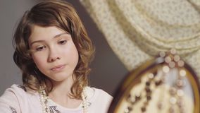 Μικρό κορίτσι που εξετάζει την αντανάκλαση καθρεφτών, που εγκαθιστά το σκουλαρίκι της μητέρας, παιδική ηλικία απόθεμα βίντεο