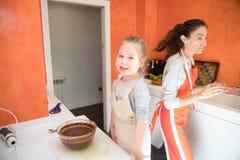 Μικρό κορίτσι που εξετάζουν και μητέρα που μαγειρεύει ένα κέικ στην κουζίνα στοκ εικόνα με δικαίωμα ελεύθερης χρήσης