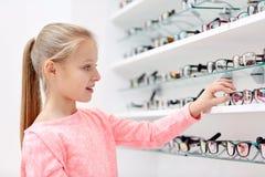Μικρό κορίτσι που επιλέγει τα γυαλιά στο κατάστημα οπτικής Στοκ εικόνα με δικαίωμα ελεύθερης χρήσης