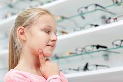 Μικρό κορίτσι που επιλέγει τα γυαλιά στο κατάστημα οπτικής Στοκ εικόνες με δικαίωμα ελεύθερης χρήσης