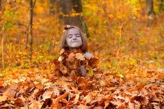 Μικρό κορίτσι που θάβεται στα φύλλα πτώσης στοκ φωτογραφίες