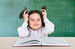Μικρό κορίτσι που διαβάζει έναν χαμογελώντας έφηβο βιβλίων κοντά σε έναν σχολικό πίνακα Στοκ Εικόνες