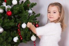 Μικρό κορίτσι που διακοσμεί το χριστουγεννιάτικο δέντρο στο σπίτι στοκ φωτογραφία με δικαίωμα ελεύθερης χρήσης