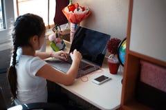 Μικρό κορίτσι που κάνει την εργασία της στο lap-top στοκ εικόνες