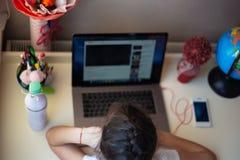 Μικρό κορίτσι που κάνει την εργασία της στο lap-top στοκ φωτογραφία με δικαίωμα ελεύθερης χρήσης