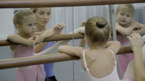Μικρό κορίτσι που κάνει το τέντωμα με το δάσκαλο στο σχολείο μπαλέτου απόθεμα βίντεο