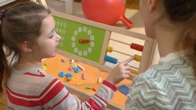 Μικρό κορίτσι που κάνει math τις ασκήσεις με τη μητέρα της στο σπίτι απόθεμα βίντεο