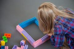 Μικρό κορίτσι που κατασκευάζει με το σύνολο κατασκευής Στοκ Εικόνες