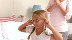 Μικρό κορίτσι που καλύπτει τα αυτιά της η κραυγή μητέρων της απόθεμα βίντεο