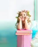 Μικρό κορίτσι που καλύπτεται με το στεφάνι και τα βιβλία στοκ φωτογραφία με δικαίωμα ελεύθερης χρήσης
