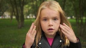 Μικρό κορίτσι που κλείνει τα μάτια της με τα χέρια της και που ανοίγει τα απόθεμα βίντεο