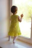 Μικρό κορίτσι που κοιτάζει στο παράθυρο Στοκ εικόνα με δικαίωμα ελεύθερης χρήσης