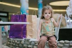 Μικρό κορίτσι που κουράζεται από τις αγορές και το κάθισμα με τις τσάντες αγορών Στοκ φωτογραφίες με δικαίωμα ελεύθερης χρήσης