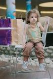 Μικρό κορίτσι που κουράζεται από τις αγορές και το κάθισμα με τις τσάντες αγορών Στοκ εικόνες με δικαίωμα ελεύθερης χρήσης