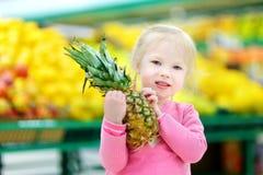 Μικρό κορίτσι που κρατά έναν ανανά σε ένα κατάστημα τροφίμων Στοκ Φωτογραφία