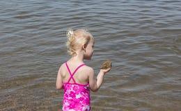 Μικρό κορίτσι που κρατά ένα ανάχωμα της λάσπης Στοκ εικόνα με δικαίωμα ελεύθερης χρήσης