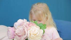 Μικρό κορίτσι που κρατά ένα μεγάλο βάζο με τα λουλούδια και τα παιχνίδια αυτοί στο δωμάτιό του στο κρεβάτι απόθεμα βίντεο