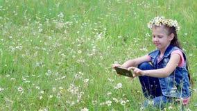 Μικρό κορίτσι που κρατά ένα τηλέφωνο, κινητός, παίρνοντας τις εικόνες τους, που παίρνουν τις φωτογραφίες ενός camomile χορτοτάπητ φιλμ μικρού μήκους
