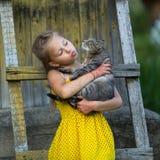 Μικρό κορίτσι που κρατά μια γάτα στα όπλα της Στοκ Φωτογραφία