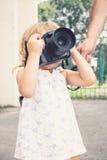 Μικρό κορίτσι που κρατά μια κάμερα και που παίρνει τις εικόνες Στοκ Φωτογραφίες