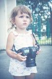 Μικρό κορίτσι που κρατά μια κάμερα και που παίρνει τις εικόνες Στοκ Εικόνα