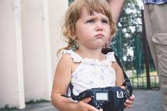 Μικρό κορίτσι που κρατά μια κάμερα και που παίρνει τις εικόνες Στοκ Φωτογραφία