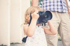 Μικρό κορίτσι που κρατά μια κάμερα και που παίρνει τις εικόνες Στοκ φωτογραφία με δικαίωμα ελεύθερης χρήσης