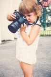 Μικρό κορίτσι που κρατά μια κάμερα και που παίρνει τις εικόνες Στοκ φωτογραφίες με δικαίωμα ελεύθερης χρήσης