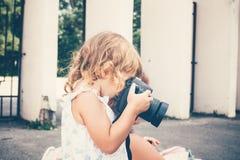 Μικρό κορίτσι που κρατά μια κάμερα και που παίρνει τις εικόνες Στοκ εικόνα με δικαίωμα ελεύθερης χρήσης