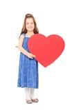 Μικρό κορίτσι που κρατά μια μεγάλη κόκκινη καρδιά Στοκ εικόνα με δικαίωμα ελεύθερης χρήσης