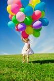 Μικρό κορίτσι που κρατά τα ζωηρόχρωμα μπαλόνια. Παιχνίδι παιδιών σε ένα πράσινο Στοκ Εικόνες