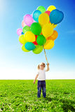 Μικρό κορίτσι που κρατά τα ζωηρόχρωμα μπαλόνια. Παιχνίδι παιδιών σε ένα πράσινο Στοκ Εικόνα