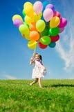 Μικρό κορίτσι που κρατά τα ζωηρόχρωμα μπαλόνια. Παιχνίδι παιδιών σε ένα πράσινο Στοκ φωτογραφία με δικαίωμα ελεύθερης χρήσης