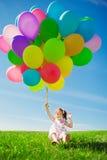 Μικρό κορίτσι που κρατά τα ζωηρόχρωμα μπαλόνια. Παιχνίδι παιδιών σε ένα πράσινο Στοκ Φωτογραφία