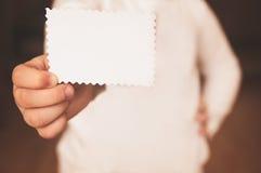 Μικρό κορίτσι που κρατά την άσπρη επαγγελματική κάρτα στοκ φωτογραφία με δικαίωμα ελεύθερης χρήσης
