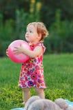 Μικρό κορίτσι που κρατά τη ρόδινη σφαίρα στο χορτοτάπητα στο πάρκο στοκ εικόνες με δικαίωμα ελεύθερης χρήσης