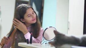 Μικρό κορίτσι που κτενίζει την εσωτερική τρίχα της που κάνει ένα hairdo το κορίτσι εφήβων ξεφυσά επάνω τη χτένα και τον καθρέφτη  φιλμ μικρού μήκους