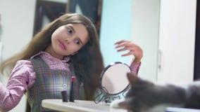 Μικρό κορίτσι που κτενίζει την τρίχα της εσωτερική κάνοντας ένα hairdo το κορίτσι εφήβων ξεφυσά επάνω τη χτένα και τον καθρέφτη τ απόθεμα βίντεο