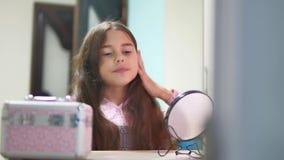 Μικρό κορίτσι που κτενίζει την τρίχα της που κάνει ένα hairdo το κορίτσι εφήβων ξεφυσά επάνω τη χτένα τρίχας και τον εσωτερικό κα απόθεμα βίντεο