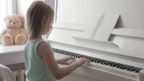Μικρό κορίτσι που μελετά για να παίξει το πιάνο στο σπίτι Προσχολικό παιδί που έχει τη διασκέδαση με την εκμάθηση να παίζεται το  φιλμ μικρού μήκους