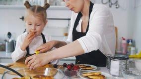 Μικρό κορίτσι που μιλά με τη μητέρα της που μαγειρεύοντας τηγανίτες τυριών εξοχικών σπιτιών στην κουζίνα Στοκ εικόνες με δικαίωμα ελεύθερης χρήσης