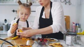 Μικρό κορίτσι που μιλά με τη μητέρα της που μαγειρεύοντας τηγανίτες τυριών εξοχικών σπιτιών στην κουζίνα Στοκ Εικόνες